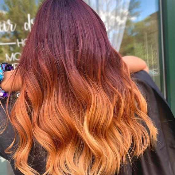 Back of woman's head with wavy hair and a mahogany to strawberry blonde dip-dye, created using Wella Professionals.