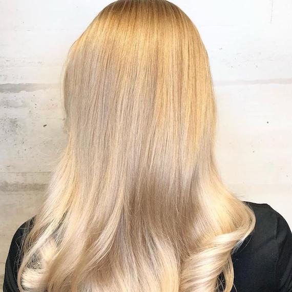 Back of woman's head with shiny blonde hair after a Wella Pure Glossing Service.