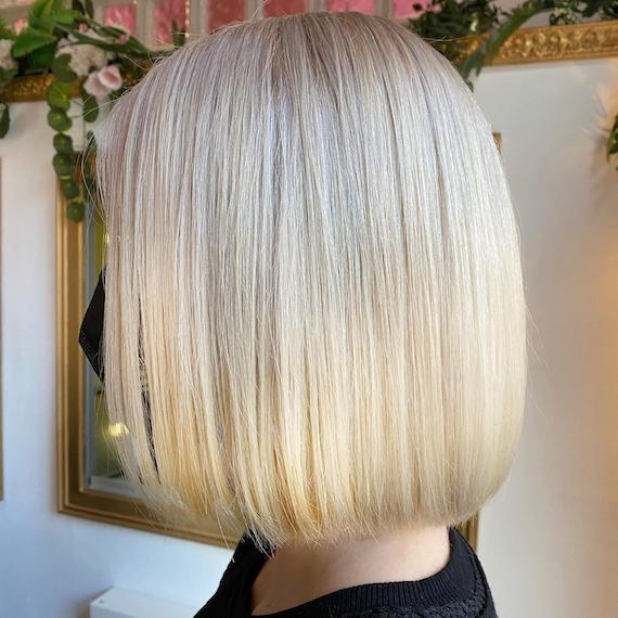 Side profile of woman with vanilla blonde bob, created using Wella Professionals.
