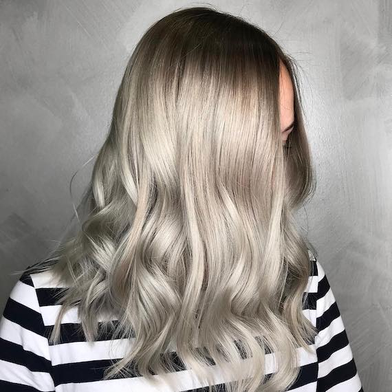 Side profile of woman with long, gray blonde hair, created using Wella Professionals.