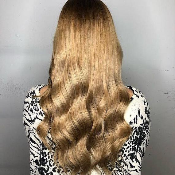 Back of woman's head with long, loosely curled, caramel blonde hair, created using Wella Professionals.