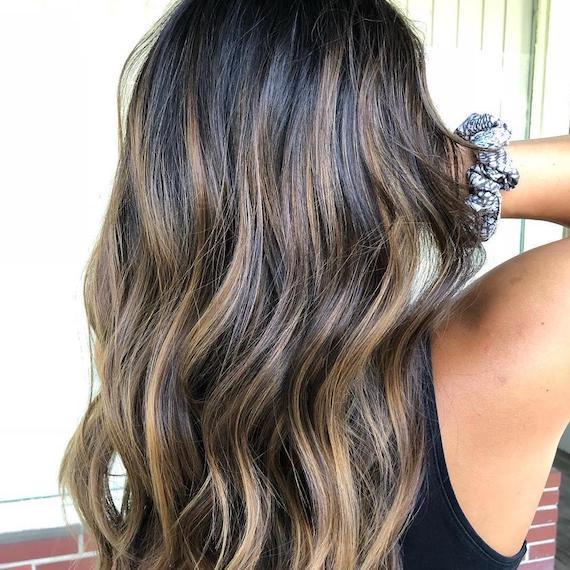 Blonde highlights through dark brunette hair, created using Wella Professionals
