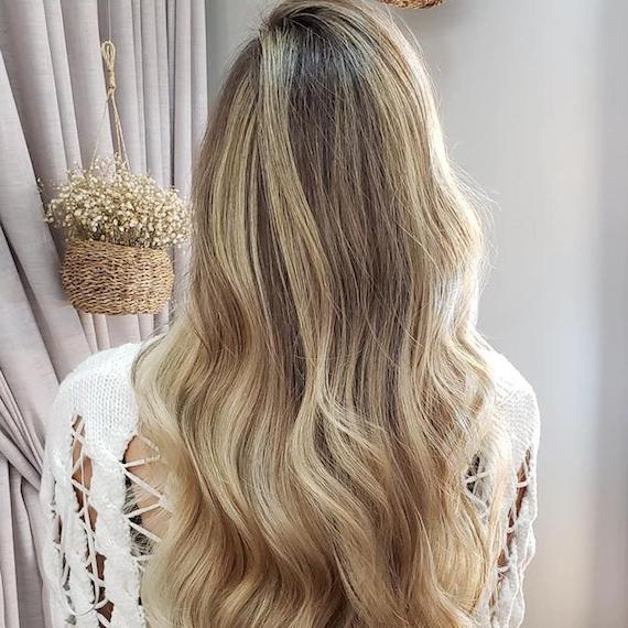 Half head of blonde highlights on long, wavy hair, created using Wella Professionals.