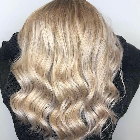 Komplettfärbung mit blonden Highlights in langem, gewelltem Haar, kreiert mit Wella Professionals.