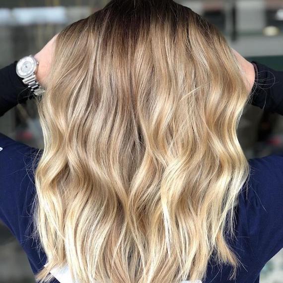 Blonde Balayage auf langem, gewelltem Haar, kreiert mit Wella Professionals.