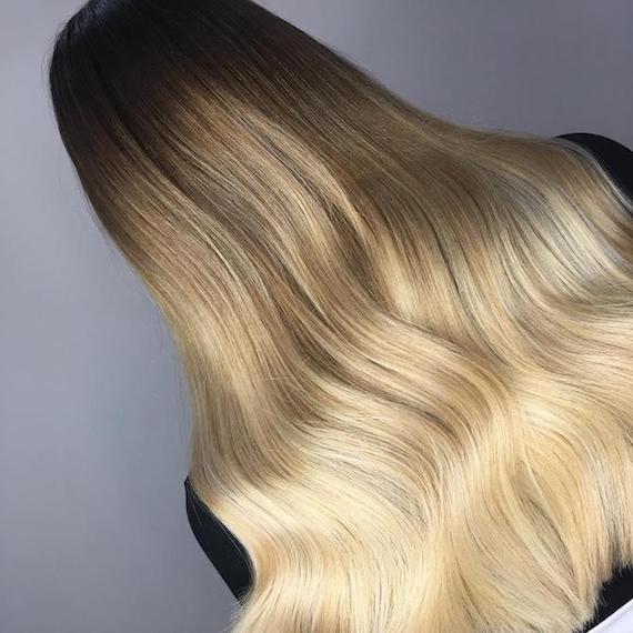 Blonde Ombré-Strähnchen in langem, gewelltem Haar, kreiert mit Wella Professionals.