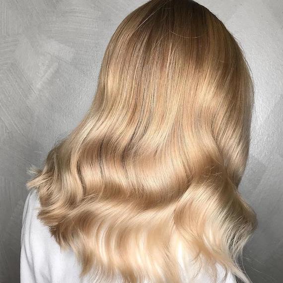 Blonde, dunkle Strähnchen in langem, gewelltem Haar, kreiert mit Wella Professionals.