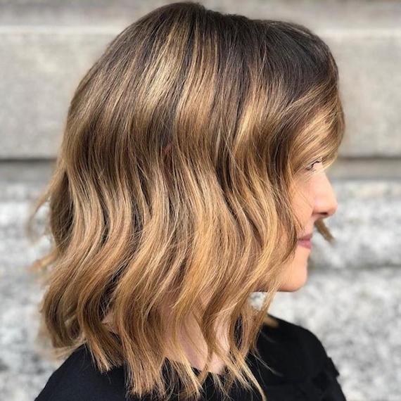 Blonde Écaille-Highlights in kurzem, welligem, braunem Haar, kreiert mit Wella Professionals.