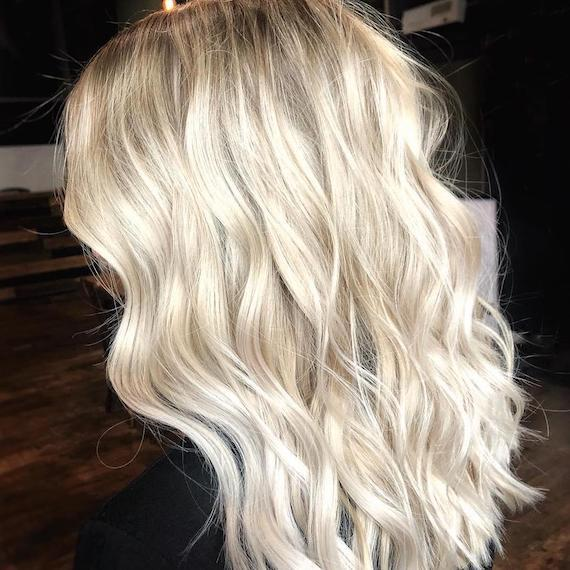 Bright blonde highlights and tousled waves, created using Wella Professionals