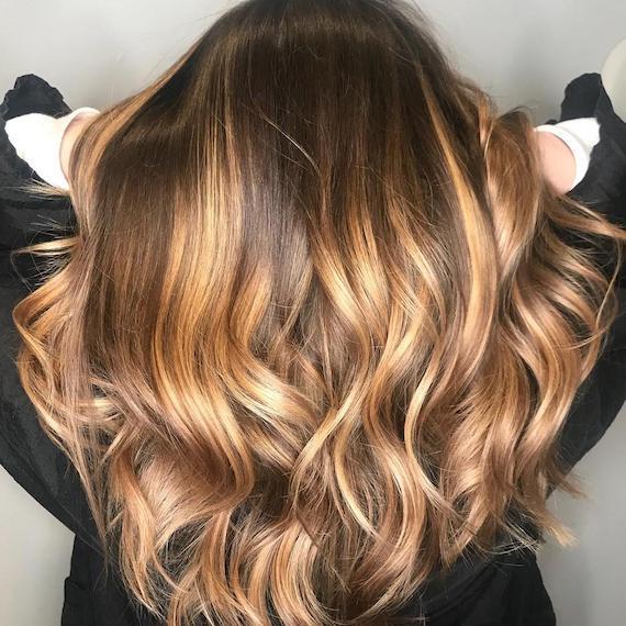 Warm blonde highlights through brown hair, created using Wella Professionals
