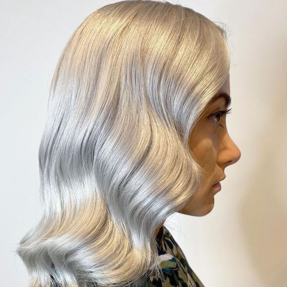 Side profile of woman with wavy white blonde hair, created using Wella Professionals.
