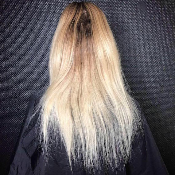 Photo of the back of a woman's head with blonde hair and dark roots.