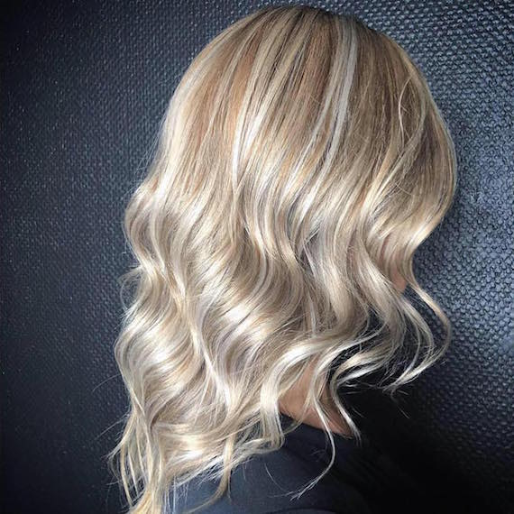 Side profile of woman with sandy blonde highlights, created using Wella Professionals.
