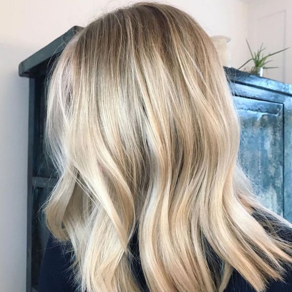 Side profile of woman with wavy, beachy blonde hair, created using Wella Professionals.