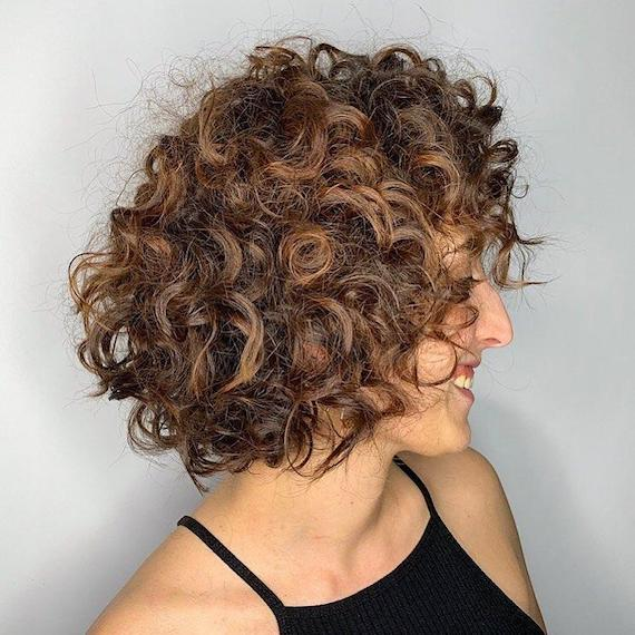 Woman with curly, brunette bob, created using Wella Professionals
