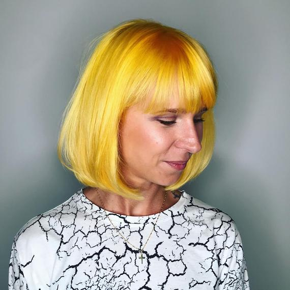 Woman with yellow bob haircut with a fringe, created using Wella Professionals