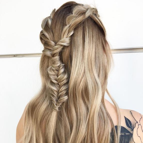 Back of woman's head with wavy, blonde hair in a half-up braid, created using Wella Professionals.