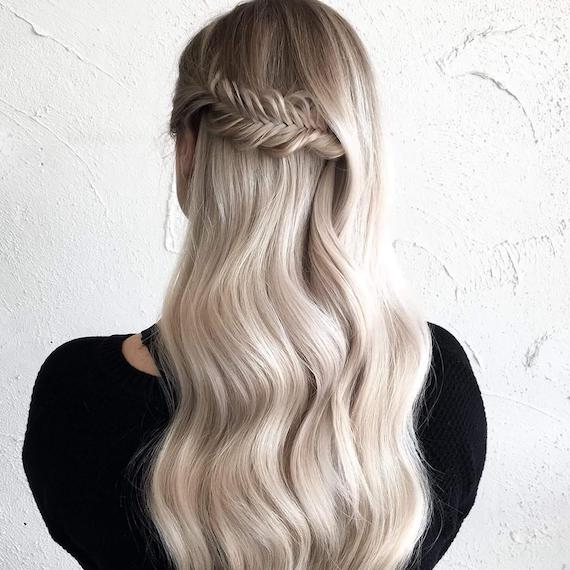 Back of woman's head with ice blonde mini fishtail braid, created using Wella Professionals.