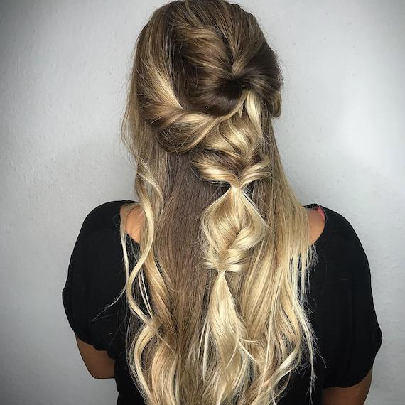 Back of woman's head with blonde, half-up twisted braid, created using Wella Professionals.