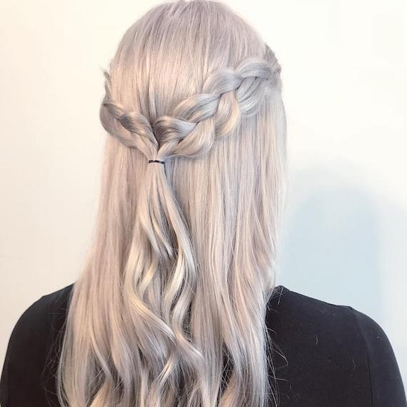 Back of woman's head with ice blonde, half-up inside out braid, created using Wella Professionals.