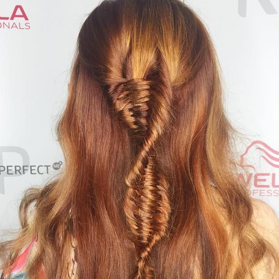 Back of woman's head with copper DNA braid, created using Wella Professionals.