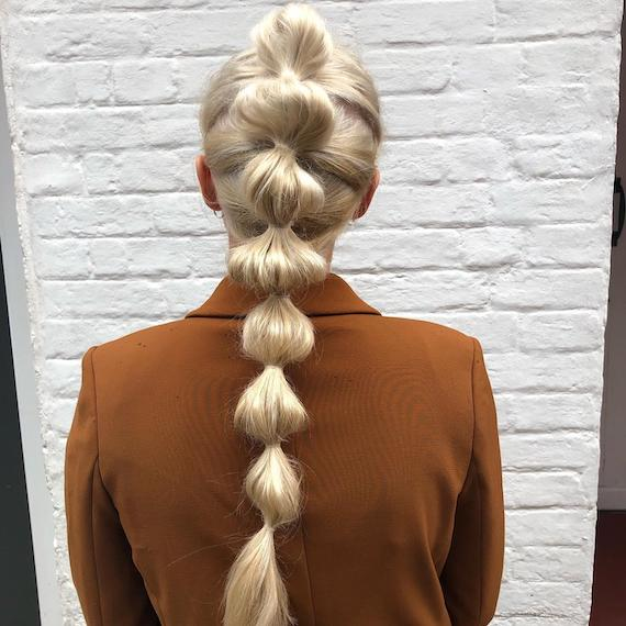 Back of woman's head with long, ice blonde bubble braid, created using Wella Professionals.