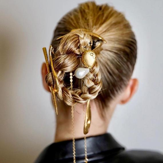 Back of woman's head with blonde braided bun, created using Wella Professionals.