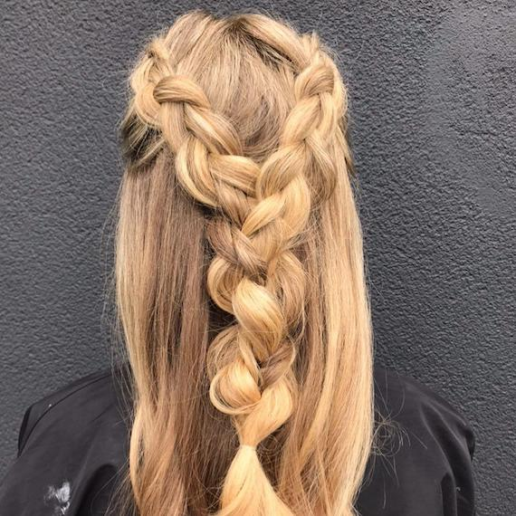Back of woman's head with blonde, half-up Dutch braid, created using Wella Professionals.