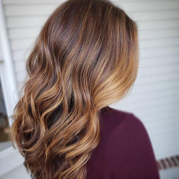 Back of woman's head with long, wavy, hair and bronde balayage, created using Wella Professionals.