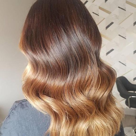Back of woman's head with long, wavy, bronde ombre hair, created using Wella Professionals.