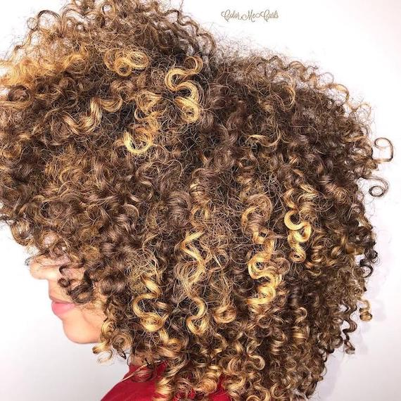 Back of woman's head with bronde curly hair, created using Wella Professionals.
