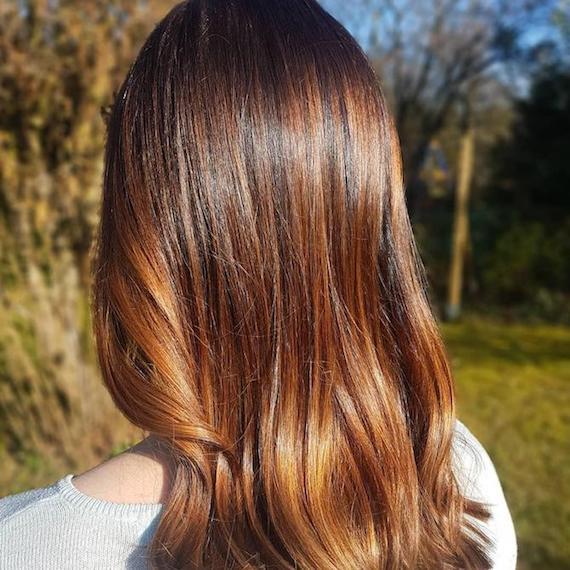 Hinterkopf einer Frau mit langem, glattem, goldbraunem Haar, das mit Wella Professionals kreiert wurde.