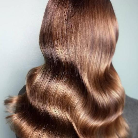 Back of woman's head with long, wavy, chestnut brown hair, created using Wella Professionals.