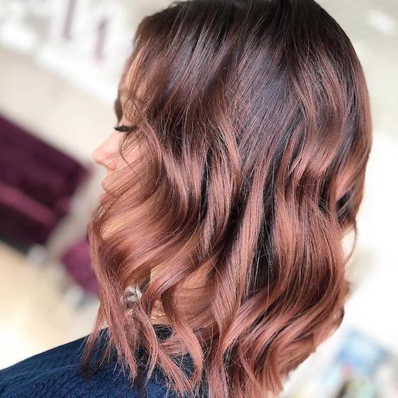 Seitenprofil einer Frau mit gewelltem, rosé-braunem Haar, kreiert mit Wella Professionals.