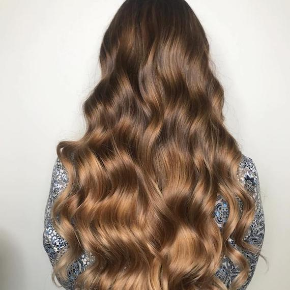 Back of woman's head with long, wavy, light brown hair, created using Wella Professionals.