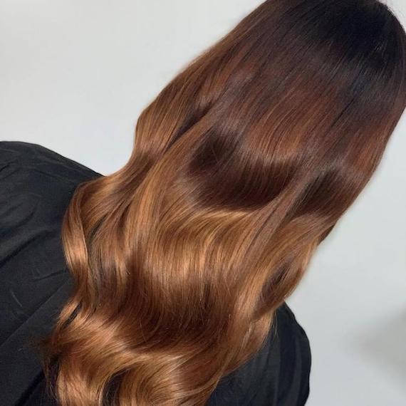 Hinterkopf einer Frau mit langem, gewelltem, schokoladenbraunem Haar, kreiert mit Wella Professionals.