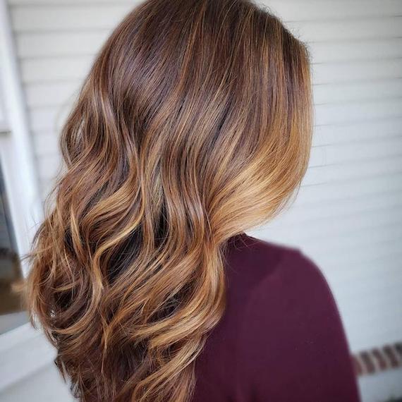 Seitenprofil einer Frau mit gewelltem, brondem Haar, kreiert mit Wella Professionals