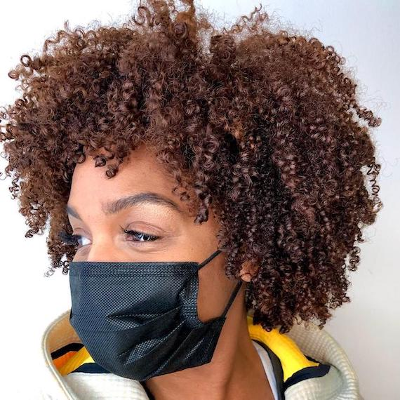 Woman wearing face mask, with curly copper brown hair created using Wella Professionals.
