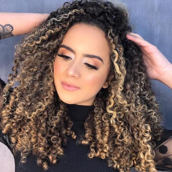Woman with dark brown curly hair and blonde highlights, created using Wella Professionals.