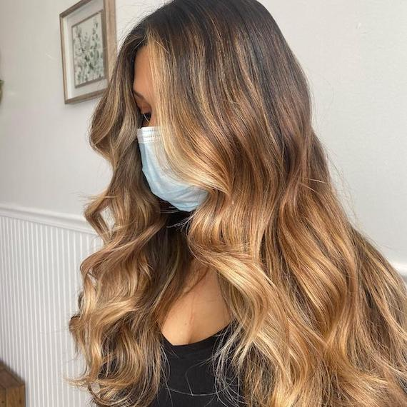 Side profile of woman with long, wavy hair and brown to blonde balayage, created using Wella Professionals.