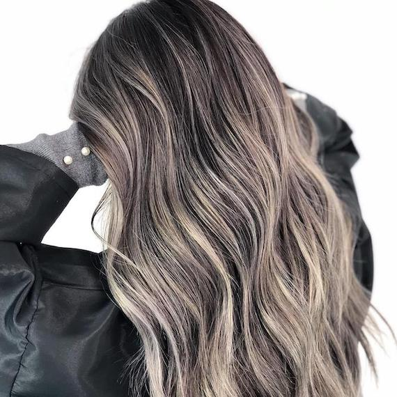 Back of woman's head with long, wavy, gray brown hair, created using Wella Professionals.