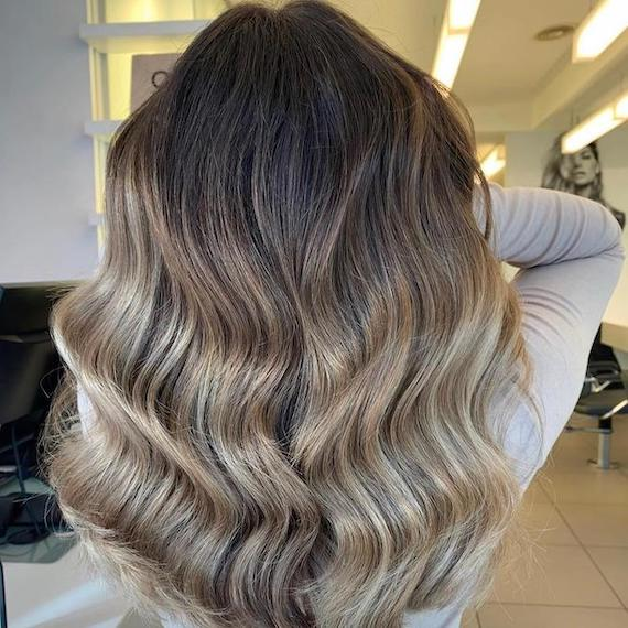 Back of woman's head with long, wavy hair and ash brown balayage, created using Wella Professionals.