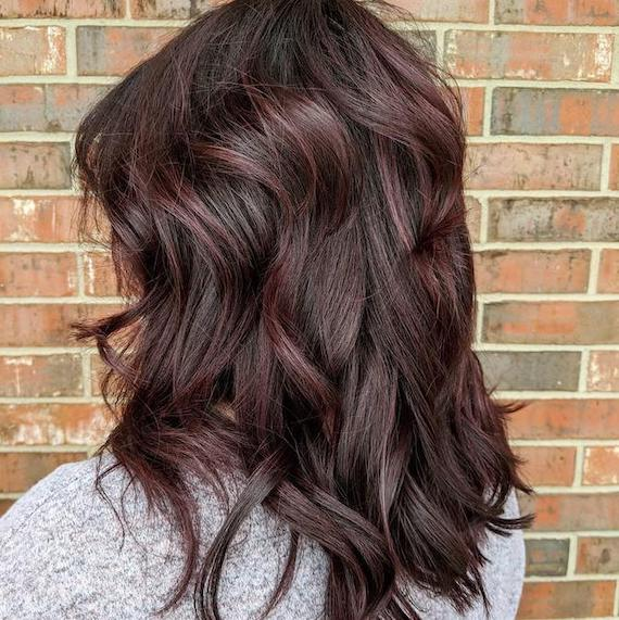Back of woman's head with tousled cherry chocolate hair, created using Wella Professionals.