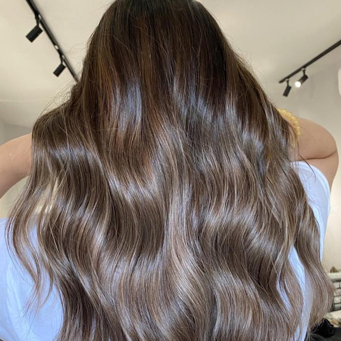 Back of woman's head with long, wavy, dark brown ombre hair, created using Wella Professionals.