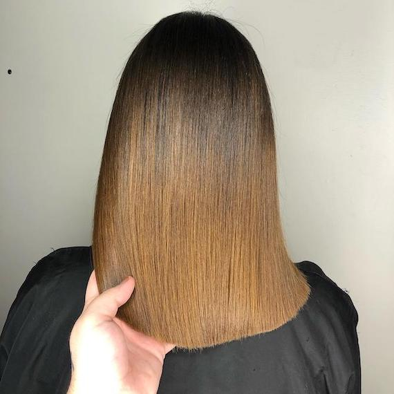 Back of woman's head with straight, golden brown ombre hair, created using Wella Professionals.