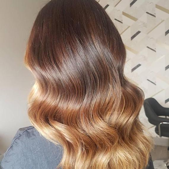 Back of woman's head with loosely curled, bronde ombre hair, created using Wella Professionals.