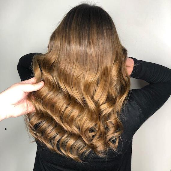 Back of woman's head with loosely curled, caramel brown ombre hair, created using Wella Professionals.