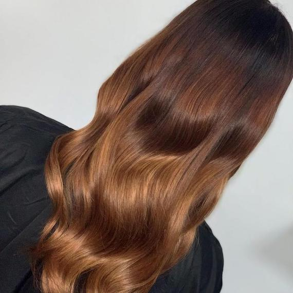 Back of woman's head with loose waves and red brown ombre hair, created using Wella Professionals.