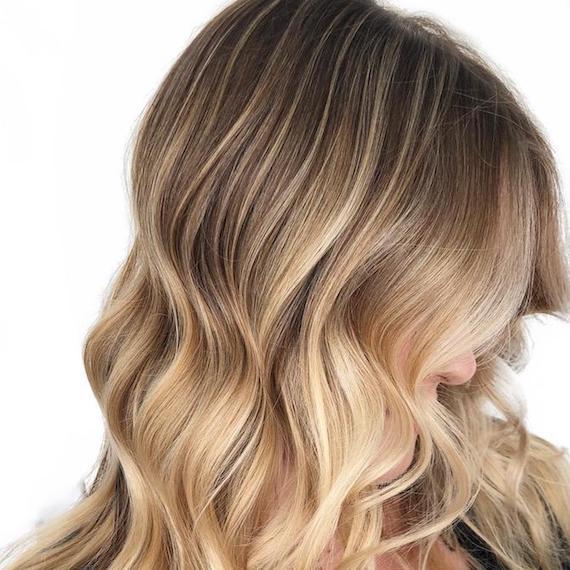 Seitenansicht einer Frau mit gewelltem, blondem Haar, kreiert mit Wella Professionals