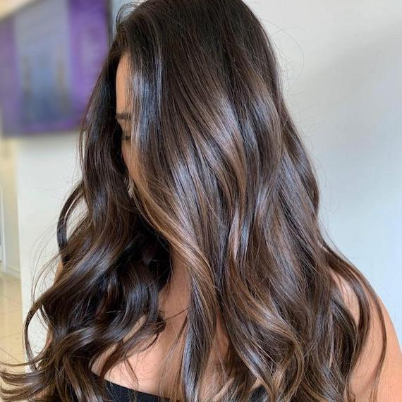 Woman with long, wavy, dark brown hair and balayage, created using Wella Professionals.
